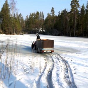 Polttopuukuorma vedettiin mönkijän avulla jäitä pitkin Myllyjärven mökille